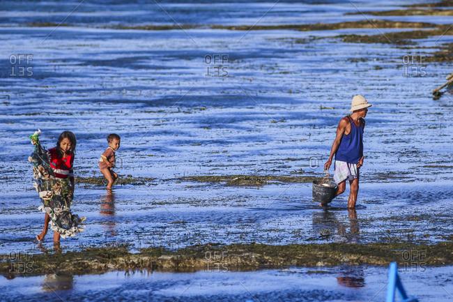 Gerupuk, Lombok, Indonesia - June 18, 2015: Indonesian family at seaweed farm