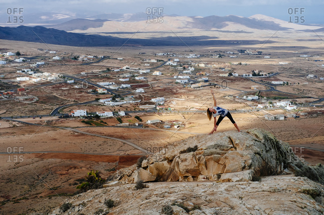 Canary Islands - May 27, 2015: Pulled back view of a girl doing yoga on top of a mountain in the desert