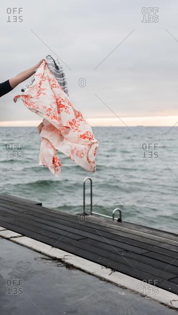 Hand holding clothes near sea