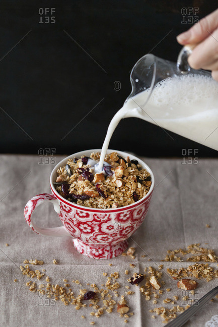 Milk being poured on homemade almond and cranberry granola