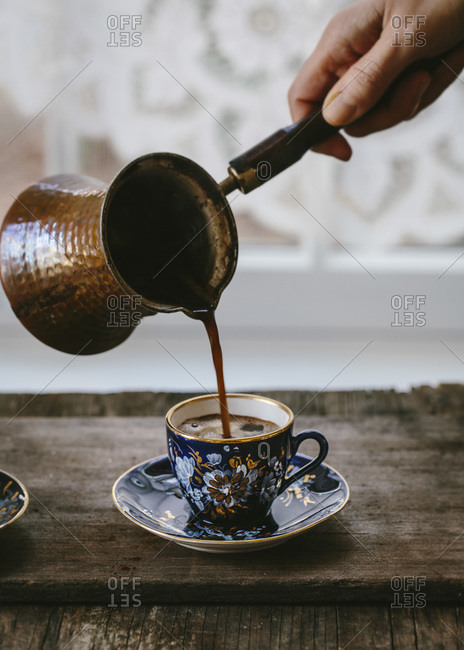 A woman is pouring Turkish coffee in to a floral demitasse cup