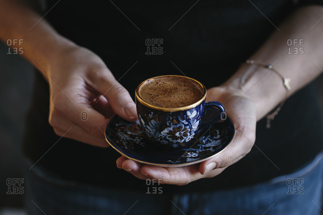 A woman holding a cup of Turkish coffee