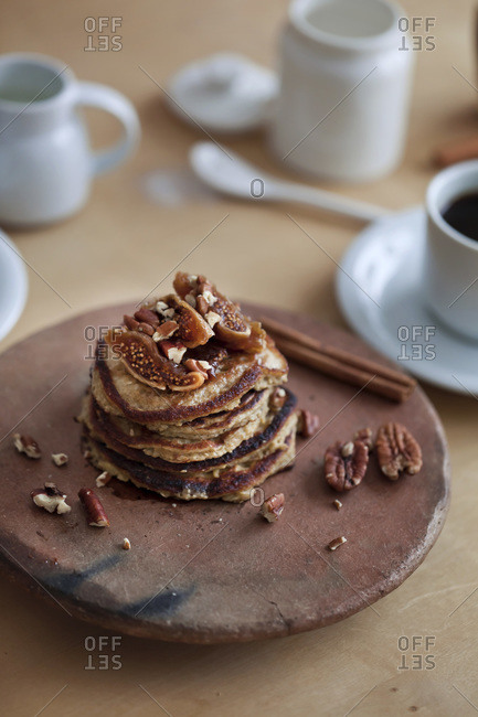 A stack of banana oat pancakes and a cup of black coffee
