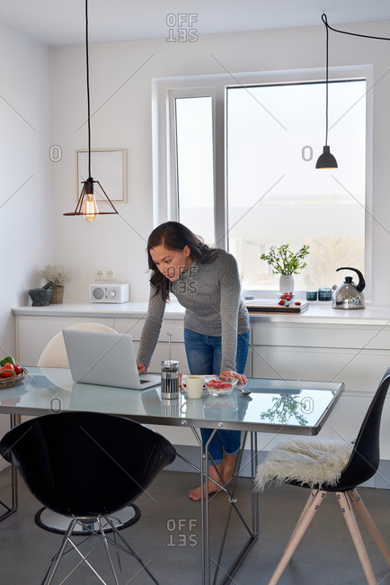 Woman checking email while having breakfast
