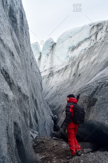 Photographer with tripod exploring a old icy glacier in Iceland