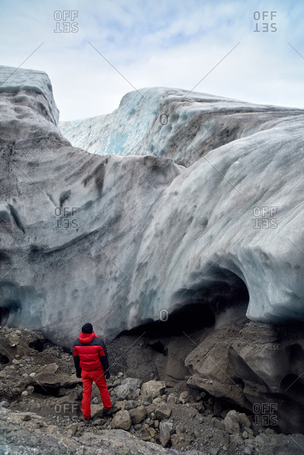 Traveler looking up at icy glacier in awe in Iceland