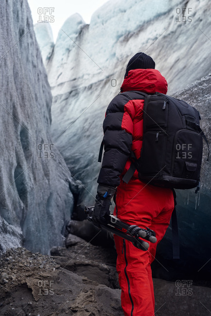 Photographer with tripod exploring icy glacier in Iceland