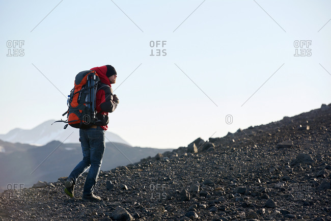 Man climbing rugged mountain with backpack and tripod in Iceland