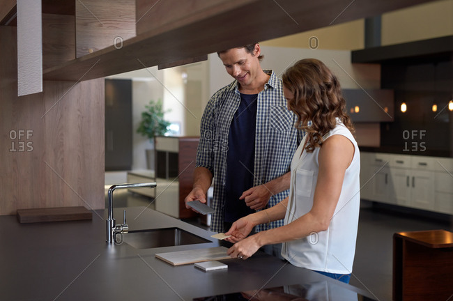 Couple choosing between kitchen counter samples in a kitchen showroom