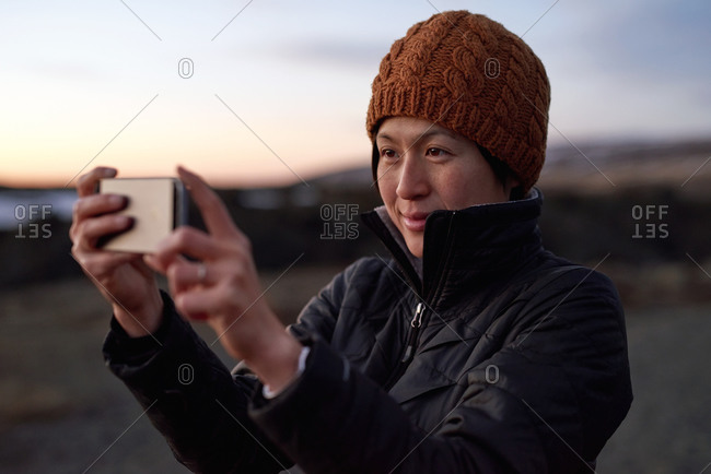 Woman taking picture taking at sunset with her cell phone