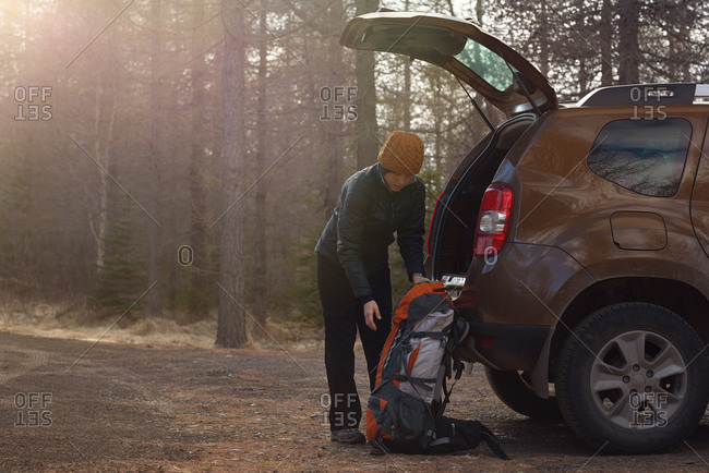 Woman hiker unpacking vehicle to go camping in the forest