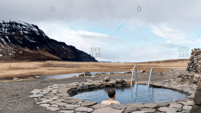 Man soaking in Iceland\'s natural hot spring