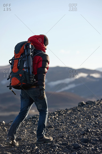 Man hiking up rugged mountain with backpack and tripod in Iceland