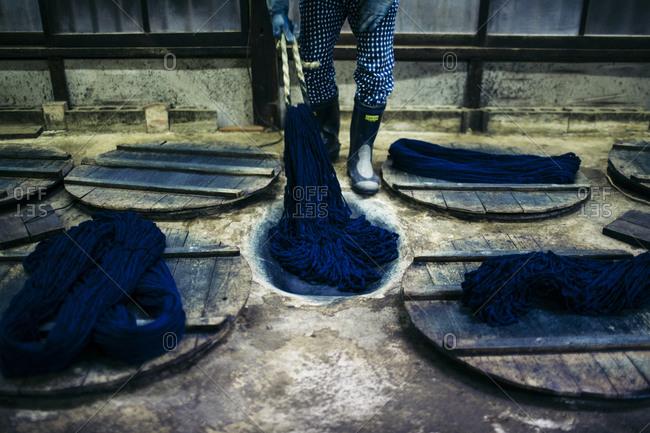 Kyushu, Japan - November 16, 2015: Man beating indigo dye into strands of cotton at the Yamamura workshop in Kyushu, Japan