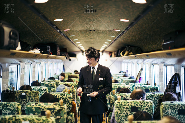Kyushu, Japan - November 17, 2015: Conductor collecting tickets on a train in Kyushu, Japan