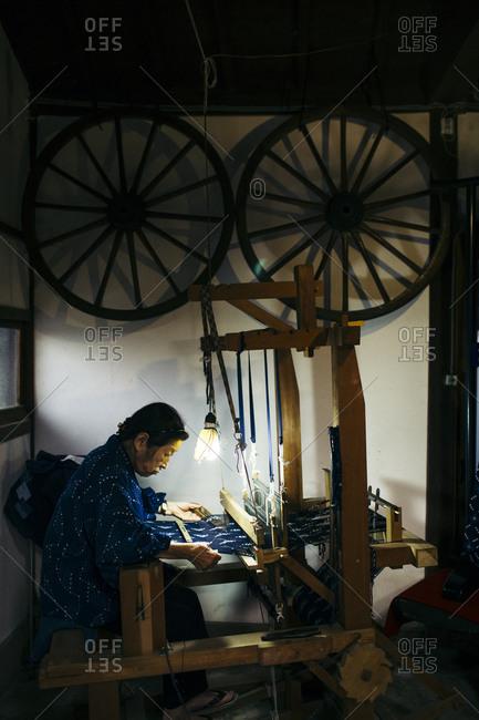 Kyushu, Japan - November 16, 2015: Elderly woman working a cotton loom at the Yamamura indigo workshop in Kyushu, Japan