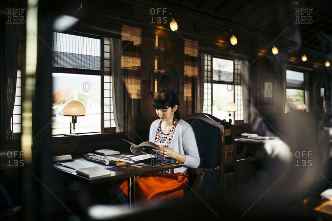 Japan - November 21, 2015: Woman reading a book at a dining table on the Seven Stars Kyushu luxury train in Japan