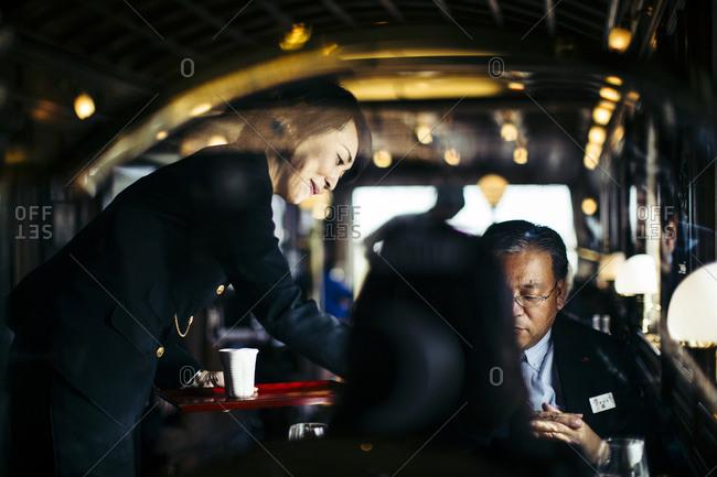 Japan - November 21, 2015: Woman serving a passenger on board the Seven Stars Kyushu luxury train in Japan