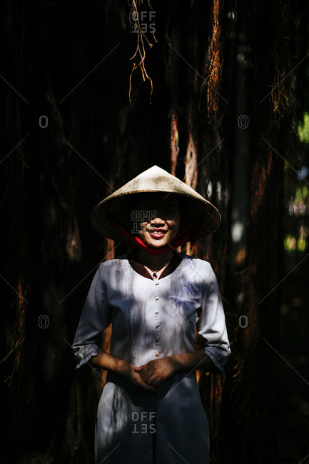 Ho Chi Minh City, Saigon, Vietnam - December 15, 2015: Young Vietnamese woman wearing an ao dai and a conical hat