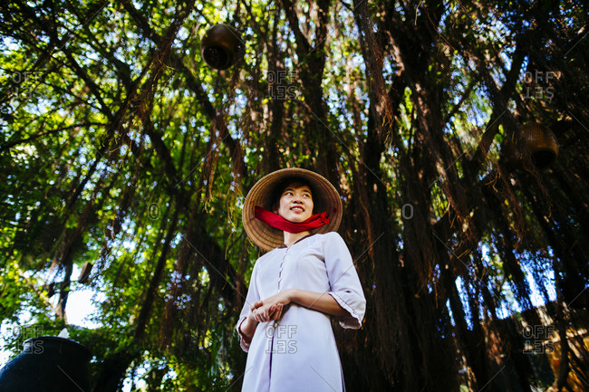 Ho Chi Minh City, Saigon, Vietnam - December 15, 2015: Young Vietnamese woman wearing an ao dai and a conical hat under a tree