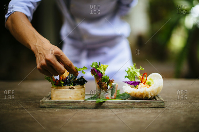 Chef putting the final touches on a dish of salads and spring rolls