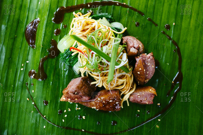 Seared duck breast and noodles served on a banana leaf
