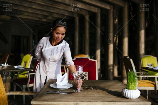 Saigon, Vietnam - December 17, 2015: Woman setting a table at a riverside restaurant at An Lam Resort in Saigon, Vietnam