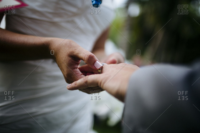 Bride putting a ring on her husband's finger during their wedding ceremony