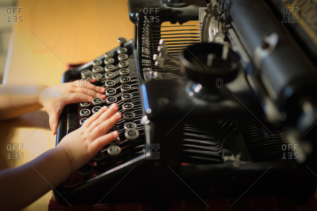 Kid's hands touching old typewriter