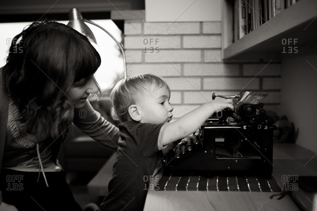 Toddler boy touching old typewriter