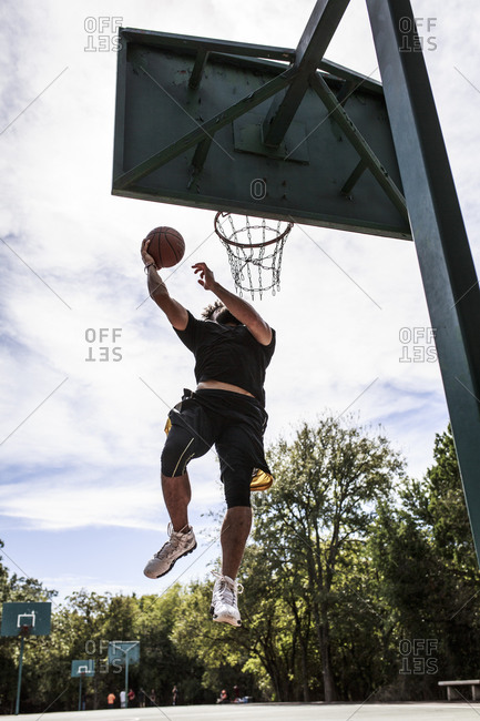 Man leaping for basketball dunk