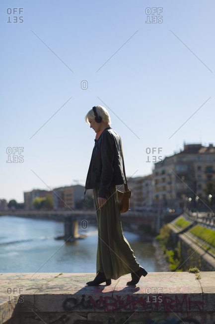 Fashionable blond woman walking on a wall listening music with headphones
