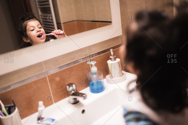 Mirror image of little girl standing in the bathroom brushing her teeth