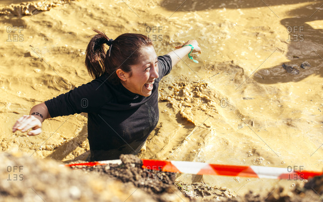 Woman in mud pit in extreme obstacle race