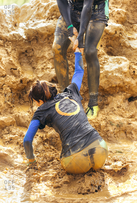 Woman being helped out of a mud pit in extreme obstacle race