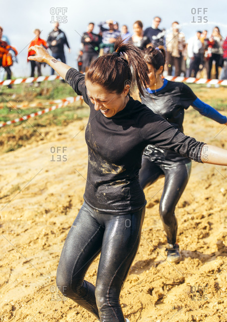 Two woman running through mud in an extreme obstacle race