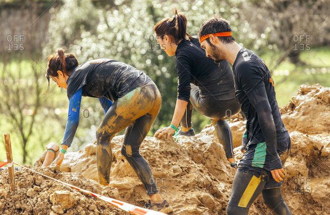 Extreme obstacle race team climbing a muddy hill