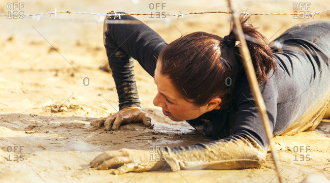 Woman in extreme obstacle race crawling on belly under barbed wire