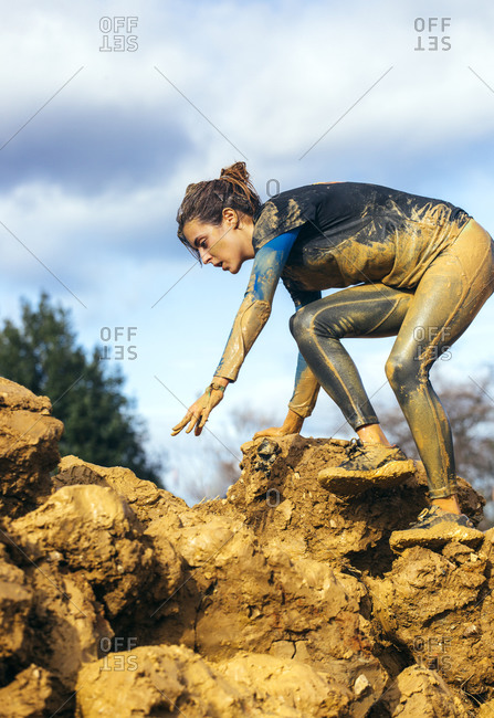 Woman in extreme obstacle race climbing down muddy rocks