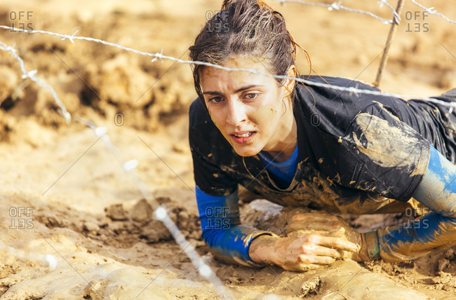 Woman in extreme obstacle race crawling under barbed wire