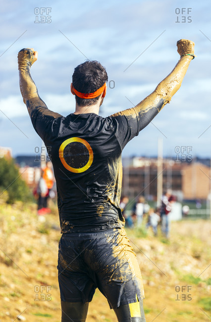 Rear view of man in extreme obstacle race cheering for his team
