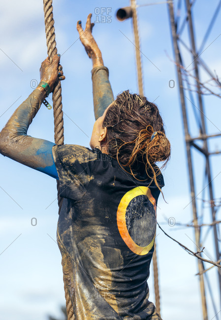 Participant in extreme obstacle race climbing up a rope