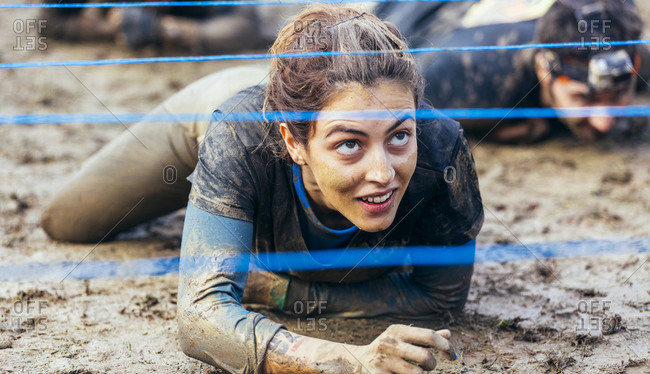 Woman in extreme obstacle race crawling under electric wire