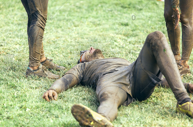 Participant in extreme obstacle race lying exhaustedly on grass