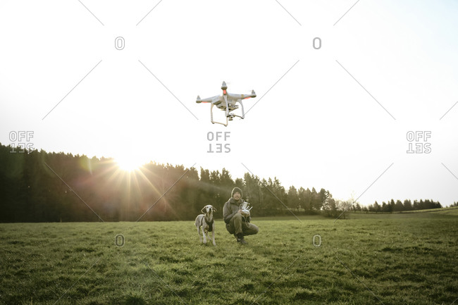 Man in a meadow with his dog flying a drone