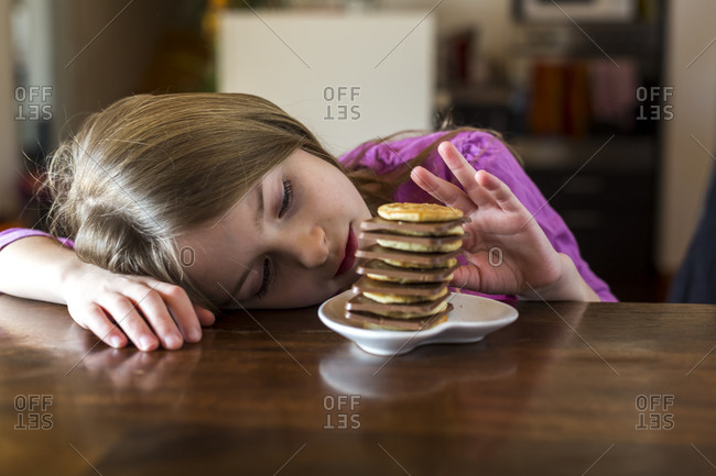 Girl with stack of mini pancakes and chocolate