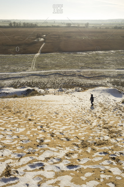 Boy on sand dune in winter