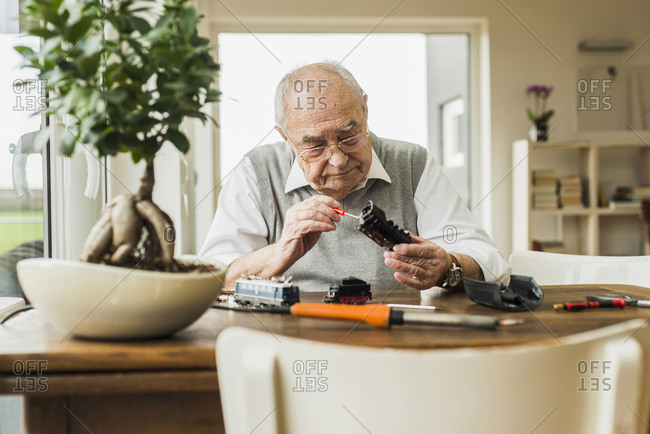 Senior man repairing toy train at home