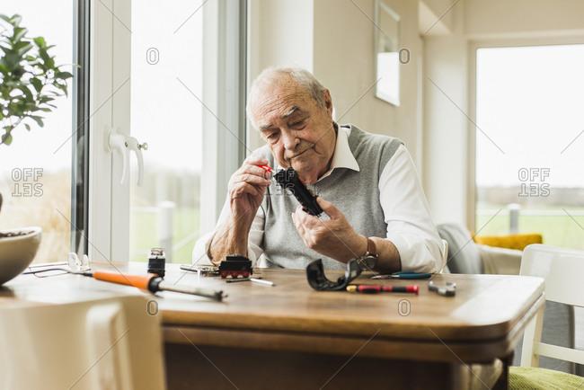 Senior man repairing toy train