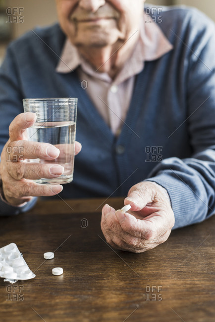Senior man taking medicine, close-up
